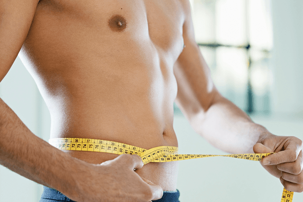 Man measuring his fit abdomen with a measuring tape